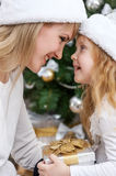 Mom with a child under the Christmas tree Stock Images