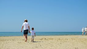 Mom and child walk along the sea sandy beach holding hands during a sunny day. Concept of travel, vacation and happy