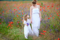 Mom and child walking holding hands outdoors. Two women in dress Royalty Free Stock Image