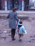 Mom and child crossing muddy road Stock Photos
