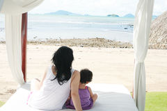 Mom with a child watching the beach on the bed Stock Images