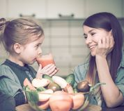 Mom with children in the kitchen prepares juice fresh royalty free stock photos