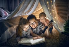 Mom and children reading book. Family bedtime. Mom and children daughters are reading a book in tent. Pretty young mother and lovely girls having fun in children Royalty Free Stock Photography