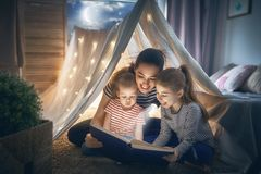 Mom and children reading book Stock Images