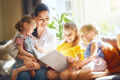 Mom and children reading a book. Happy loving family. pretty young mother reading a book to her daughters stock image
