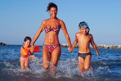 Mom and children running in the sea royalty free stock image
