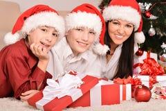 Mom and children in santa hats Stock Photo