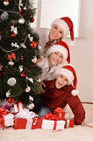 Mom and children in santa hats Royalty Free Stock Photos