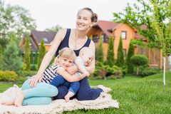 Mom with children sitting on a green grass lawn in park. Young mother with daughter and son having fun on picnic at backyard on br stock image