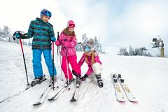 Mom with children on ski terrain preparing daughter for skiing. Mom with children on ski terrain preparing daughters ski shoes for skiing Stock Photography