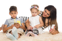 Mom and children with smartphones Stock Images