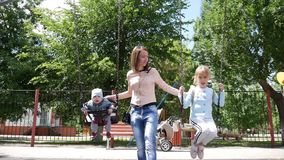 Mom children swing in the park lifestyle active. Mom children swing in the park lifestyle active stock video footage
