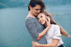 Mom with children walking outdoor. Mom and her teenage daughter hugging and smiling together over blue sea view Royalty Free Stock Photo