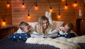 Mom with children in the winter frosty evening sitting on the bed and reading a book together. stock image