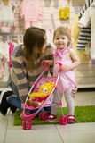 Mom choose the doll for my daughter. A young mother wraps a new doll for her little daughter in a children`s store Stock Photography