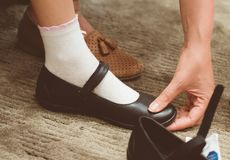 Mom chooses shoes for her daughte. Mom chooses shoes for her daughter in the store royalty free stock photography