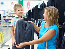 Mom chooses suit for little son Stock Images