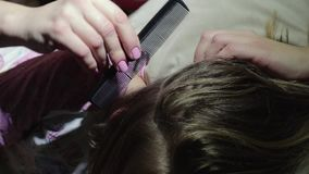 Treatment of head pediculosis in a child, removal of nits and lice in the girl`s hair