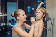 Mom cleans his son`s teeth before going to sleep on a background of a night city stock photo