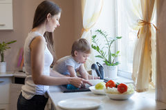 Mom cleans the vegetables in the kitchen. Boy it interferes stock photography