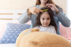 Mom comb her lovely little asian daughter on bed at bedroom. Cute Asia child is innocent girl. Nursery child feel happy and royalty free stock images