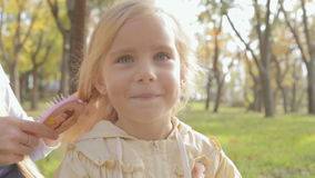 Mom combing hair of little cute blond daughter on stock video footage
