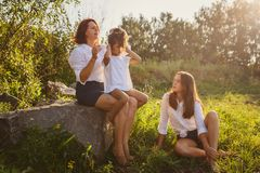 Mom combs her daughter`s hair in nature stock image