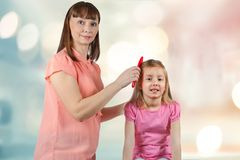 Mom combs her little daughter`s hair. Blurred background with beautiful bokeh Stock Images