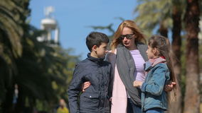 Mom comforts quarreled brother and sister in the street against the backdrop of palm trees. Mom comforts quarreled brother and sister, in the street against the stock footage