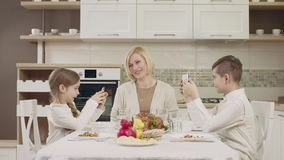 Mom communicates with her children at the table during a family dinner