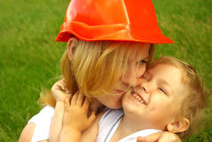 Mom in the construction helmet with love hugging happy daughter Royalty Free Stock Images