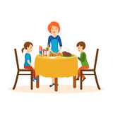 Mom cooks on a dinner, children sit of the table. Mom cooks on a cutting board dinner, standing at the table, two young children sitting on both sides of the Stock Photo
