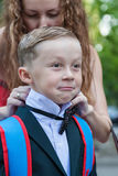 Mom corrects bow-tie son Royalty Free Stock Photography