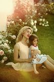 Mom cuddling daughter on green grass on sunny summer day. Childhood and parenting. Family love and care. Woman with girl child at blossoming rose flowers royalty free stock photos