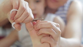Mom cut off the baby`s nails on the legs close-up from the child. Cutting the children`s nails stock video footage