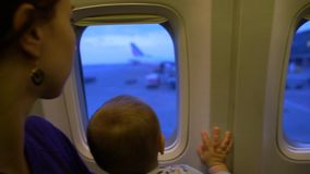 The mom and baby look out the window of the plane in slow motion. The mom and cute baby look out the window of the plane before takeoff. Action in slow motion stock video footage