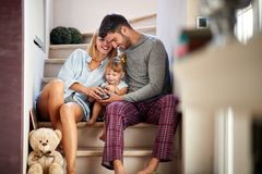 Mom and dad with adorable kid on stairs stock image