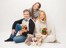 Mom, dad and adult daughter on white background with soft toys. A family business for sewing soft cute toy bears. Family with toys on a white background Stock Photo