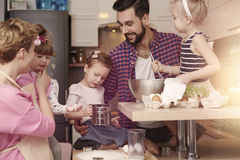 Mom and dad with baby girls baking Stock Images