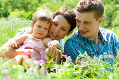 Mom, dad and baby in grass. Mom, dad and baby playing in the grass Royalty Free Stock Image