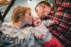 Mom, dad and baby lie on a woolen carpet and smile. On the floor Stock Image