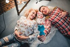 Mom, dad and baby lie on a woolen carpet and smile. On the floor Royalty Free Stock Photos
