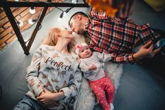 Mom, dad and baby lie on a woolen carpet and smile. On the floor Stock Photography