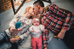 Mom, dad and baby lie on a woolen carpet and smile. On the floor Stock Photo