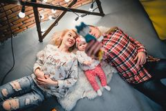 Mom, dad and baby lie on a woolen carpet and smile. On the floor Royalty Free Stock Images