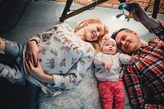 Mom, dad and baby lie on a woolen carpet and smile. On the floor Stock Images