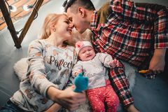 Mom, dad and baby lie on a woolen carpet and smile. On the floor Stock Photos