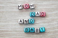 Mom dad and baby sign. MOM DAD AND BABY cube blocks arranged on gray wooden background Stock Photography