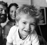 Mom, dad and boy in light room and blackboard on background, defocused. Love and family games concept. Young family. Spends time in study room. Parents and son royalty free stock photography