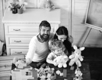 Mom, dad and boy play with white soft toys. On room background. Parents and son with cheerful faces near colorful blocks for building. Young family spends time royalty free stock photography